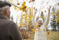 Playful senior couple throwing autumn leaves overhead in park