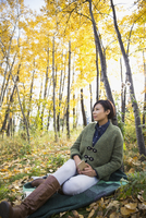 Pensive woman with cell phone relaxing on blanket in autumn woods 11096046662| 写真素材・ストックフォト・画像・イラスト素材|アマナイメージズ