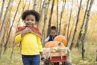 Portrait smiling sisters pulling wagon with autumn pumpkins in woods