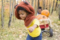 Girl sisters pulling wagon with autumn pumpkins in autumn woods