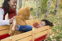 Playful mother and daughter in wagon with teddy bear in autumn woods
