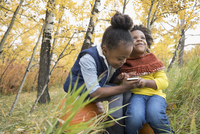 Smiling girls sitting on pumpkins texting with cell phone in autumn woods