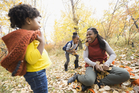 Mother and daughters playing throwing autumn leaves in park
