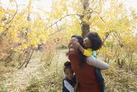 Mother piggybacking daughter in autumn woods