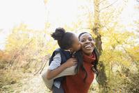 Daughter kissing mother in autumn woods 11096046712| 写真素材・ストックフォト・画像・イラスト素材|アマナイメージズ