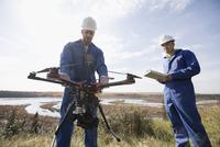 Surveyors with drone equipment on sunny hilltop overlooking lake 11096046728| 写真素材・ストックフォト・画像・イラスト素材|アマナイメージズ