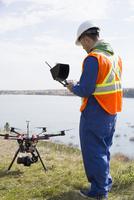 Surveyor with drone equipment at sunny lakeside 11096046729| 写真素材・ストックフォト・画像・イラスト素材|アマナイメージズ