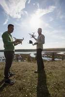 Male friends with drone equipment on sunny hilltop overlooking lake 11096046736| 写真素材・ストックフォト・画像・イラスト素材|アマナイメージズ