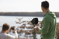 Male friends with drone equipment and camera phone overlooking lake 11096046742| 写真素材・ストックフォト・画像・イラスト素材|アマナイメージズ