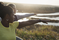 Women practicing yoga warrior 2 pose on sunny autumn hilltop 11096046777| 写真素材・ストックフォト・画像・イラスト素材|アマナイメージズ
