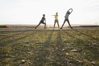Women stretching exercising in sunny autumn park 11096046784| 写真素材・ストックフォト・画像・イラスト素材|アマナイメージズ