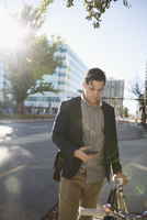 Businessman texting with cell phone commuting with bicycle on urban sidewalk