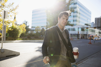 Portrait businessman with coffee commuting with bicycle on sunny urban sidewalk 11096046976| 写真素材・ストックフォト・画像・イラスト素材|アマナイメージズ
