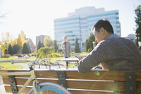 Businessman texting with cell phone on sunny urban park bench