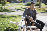 Portrait confident businessman commuter with bicycle on sunny park bench