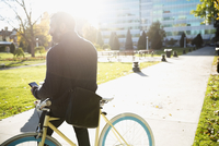 Businessman commuting with bicycle texting with cell phone in sunny urban park