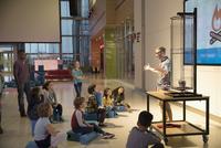 Children watching scientist leading demonstration in science center 11096047000| 写真素材・ストックフォト・画像・イラスト素材|アマナイメージズ