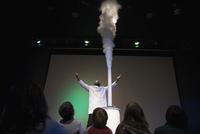 Children watching scientist demonstrating geyser cloud in science center theater