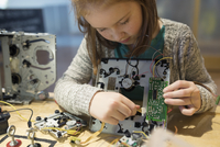 Girl assembling circuit board electronics in science center
