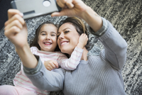 Overhead view enthusiastic mother and daughter taking selfie laying on rug 11096047393| 写真素材・ストックフォト・画像・イラスト素材|アマナイメージズ