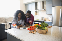 Couple drinking sangria and using digital tablet in kitchen 11096047419| 写真素材・ストックフォト・画像・イラスト素材|アマナイメージズ