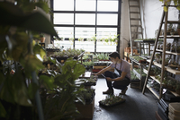 Male shop owner with digital tablet taking inventory in plant shop