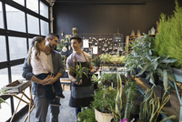 Male shop owner helping father and daughter shopping in plant shop 11096047575| 写真素材・ストックフォト・画像・イラスト素材|アマナイメージズ