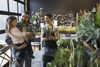 Male shop owner helping father and daughter shopping in plant shop 11096047576| 写真素材・ストックフォト・画像・イラスト素材|アマナイメージズ