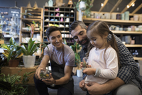 Male shop owner helping father and daughter shopping browsing terrariums in plant shop