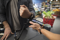 Close up male shopper paying with smart watch contactless payment at plant shop 11096047578| 写真素材・ストックフォト・画像・イラスト素材|アマナイメージズ