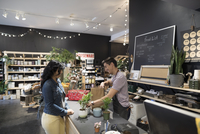 Male shop owner helping female customer buying plants at shop counter 11096047580| 写真素材・ストックフォト・画像・イラスト素材|アマナイメージズ