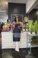 Portrait confident female shop owner at counter in plant shop