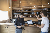 Male brewers with clipboard and laptop examining beer in brewery tasting room