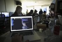 Personal perspective hacker coding on laptop at hackathon in dark office 11096047747| 写真素材・ストックフォト・画像・イラスト素材|アマナイメージズ