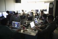 Hackers working hackathon at laptops in dark office 11096047753| 写真素材・ストックフォト・画像・イラスト素材|アマナイメージズ
