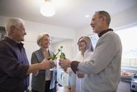 Senior couples toasting beer bottles in kitchen 11096048117  写真素材・ストックフォト・画像・イラスト素材 アマナイメージズ