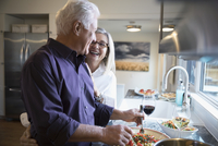 Affectionate senior couple laughing cooking and drinking wine in kitchen