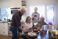 Senior couple friends celebrating birthday with fireworks cake 11096048140| 写真素材・ストックフォト・画像・イラスト素材|アマナイメージズ