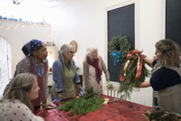 Instructor teaching women in wreath making art and craft class