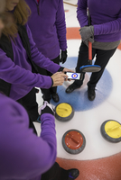 Female curling team scoring with mobile app on smart phone