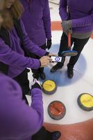 Female curling team scoring with mobile app on smart phone 11096048308| 写真素材・ストックフォト・画像・イラスト素材|アマナイメージズ
