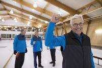 Portrait confident senior man gesturing at curling club