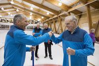 Senior men fist bumping at curling club
