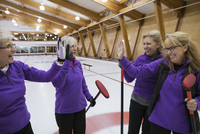 Smiling senior women curling and high-fiving