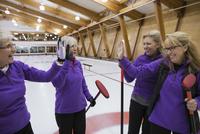 Smiling senior women curling and high-fiving 11096048345| 写真素材・ストックフォト・画像・イラスト素材|アマナイメージズ