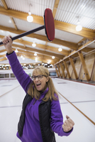 Enthusiastic woman with curling broom cheering 11096048348| 写真素材・ストックフォト・画像・イラスト素材|アマナイメージズ