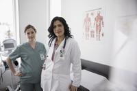 Portrait confident female doctor and pregnant nurse in clinic examination room 11096048517  写真素材・ストックフォト・画像・イラスト素材 アマナイメージズ