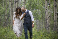 Affectionate bride and groom holding hands and walking in woods