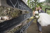 Affectionate bride and groom kissing next to Happily Ever After sign 11096048781| 写真素材・ストックフォト・画像・イラスト素材|アマナイメージズ