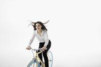 Smiling businesswoman riding bicycle against white background 11096049069| 写真素材・ストックフォト・画像・イラスト素材|アマナイメージズ